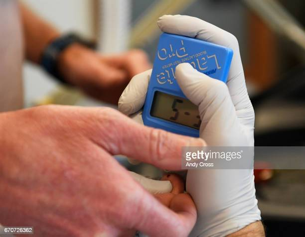 Dr Inigo San Millan takes a blood sample from triathlete Zach Barber with a lactate take meter during a metabolic and physiologic test in a lab at...