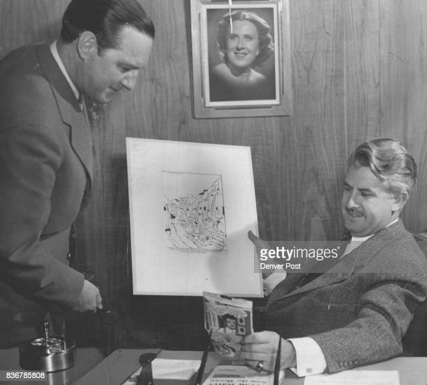 Dr Irving P Krick and his assistant Charles A Warner compare Lichty's original 'cloud seeding' cartoon for his 'Grin and Bear It' strip with the...