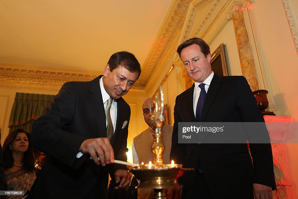 Dr. Jaimini Bhagwati the High Commissioner of India to the United Kingdom (L) lights a flame with the British Prime Minister <a gi-track='captionPersonalityLinkClicked' href=/galleries/search?phrase=David+Cameron+-+Politician&family=editorial&specificpeople=227076 ng-click='$event.stopPropagation()'>David Cameron</a> at Number 10 Downing Street on November 19, 2012 in London, England.