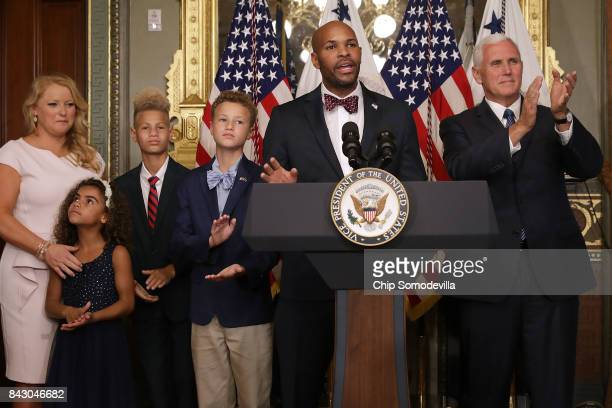 Dr Jerome Adams delivers remarks after being sworn in as US Surgeon General during a ceremony with his family wife Lacey Adams and Vice President...
