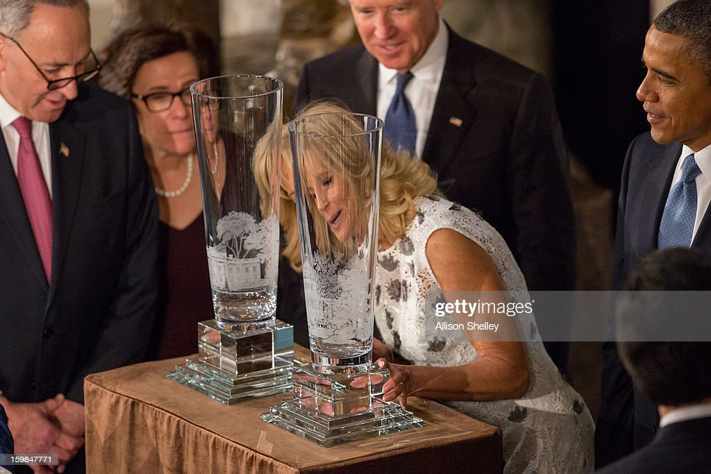 Dr. Jill Biden touches hand-cut and etched crystal vases created by Lenox as her husband, U.S. Vice President Joseph Biden and President Barack Obama look on during the Inaugural Luncheon in Statuary Hall on inauguration day at the U.S. Capitol building January 21, 2013 in Washington D.C. The vases were given to the two couples as gifts. Obama and Biden were ceremonially sworn in for his second term today.