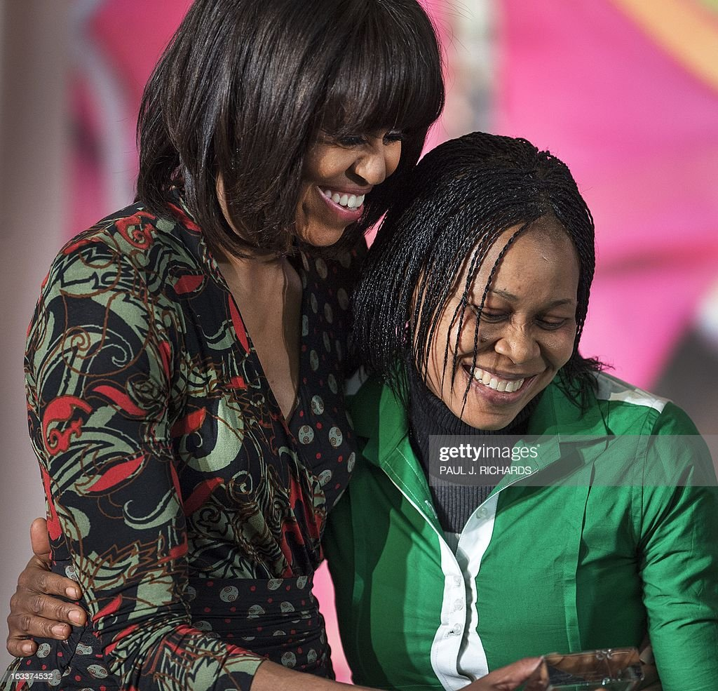 Dr. Josephine Obiajulu Odumakin of Nigeria is hugged by US First Lady Michelle Obama (R) as she is presented with the Secretary of State's International Women of Courage Award inside the Dean Acheson Auditorium of the US Department of State March 8, 2013, in Washington. The Secretary of State's International Women of Courage Award annually recognizes women around the globe who have shown exceptional courage and leadership in advocating for women's rights and empowerment, often at great personal risk. Since the inception of this award in 2007, the Department of State has honored 67 women from 45 different countries. AFP Photo/Paul J. Richards