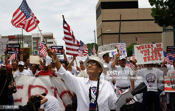 Dr Josue Elorreaga vice president of La Alianza Hispana Evangelica of DallasFort Worth waves an American flag as he joins a crowd estimated by police...