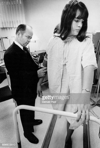 Dr Loring Brock director of cardiac reconditioning and work evaluation unit of Spalding takes blood pressure of Miss Williams Initial testing for Pam...