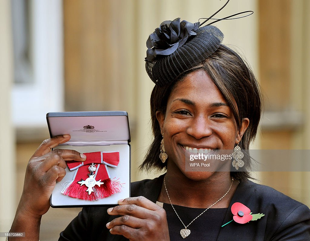 Dr Maggie Sanni-Alphonsi proudly holds her Member of the British Empire (MBE) medal following an Investiture Ceremony hosted by the Princess Royal at Buckingham Palace on November 7, 2012 in London, England.