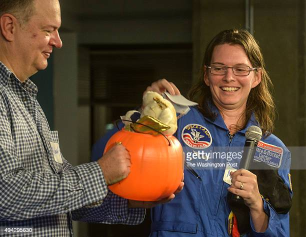Dr Malynda Chizeck Frouard right an astronomer with the Naval Observatory picks a prize out of a pumpkin held by Michael Schade after delivering her...