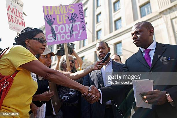 Dr Marsha ColemanAdebayo shakes hands with Justice Department Press Secretary Kevin Lewis after reading a letter for Attorney General Eric Holder...