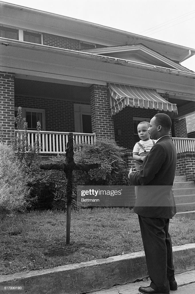 Dr Martin Luther King Jr holds his twoyear old son Martin Luther King III as he stands near a burnt cross in front of his home in Atlanta Georgia