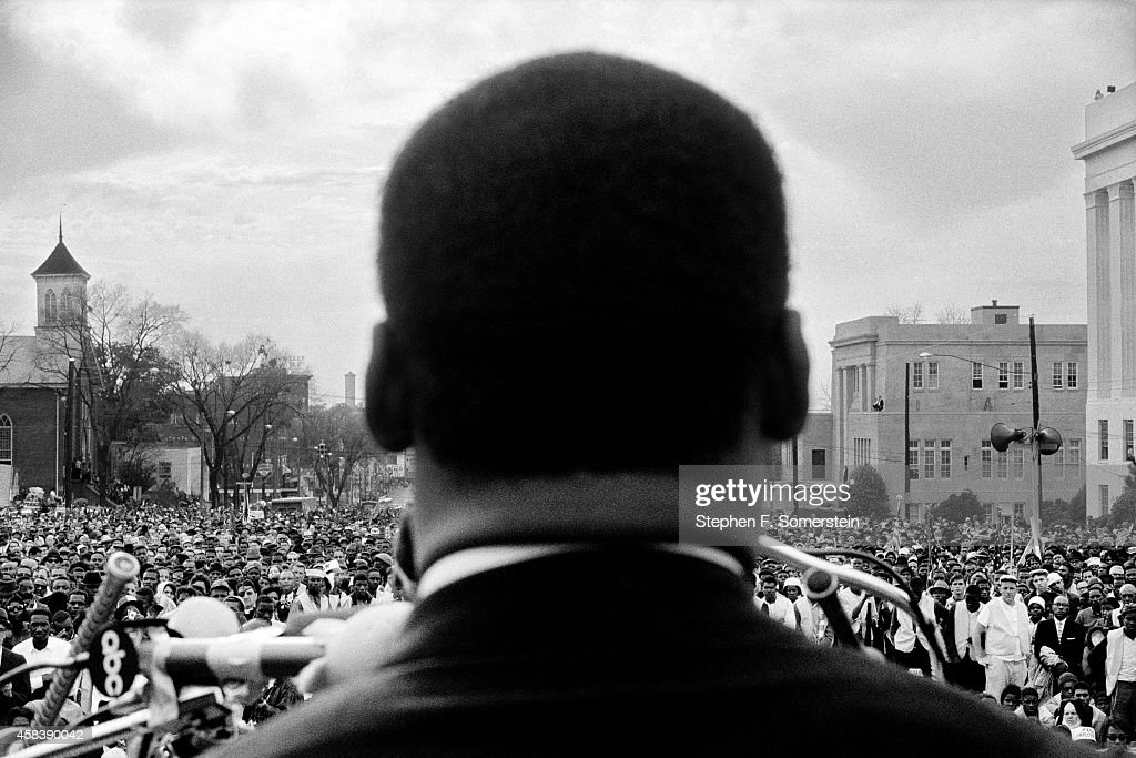 Dr. Martin Luther King, Jr. seen close from the rear, speaking in front of 25,000 civil rights marchers, at the conclusion of the Selma to Montgomery march in front of Alabama state capital building on March 25, 1965. In Montgomery, Alabama.