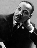 Dr Martin Luther King Jr the civil rights campaigner and famous orator portrait of a young man in a black suit and tie with his head tilted 1955