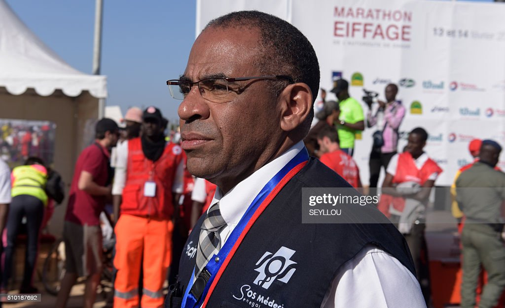 Dr Massamba Sassou Diop, head of SOS medecins Senegal and son of historian Cheikh Anta Diop stands in Dakar on February 14, 2016 during the first ever Dakar International Marathon long 42,195km in 2h 16mm 37s according to official results. The competition organised by the BTP Eiffage society started on February 13 in front of International Conference Center Abou Diouf (Cicad) on the outskirts of Dakar with different runs of 10 km and will end the day after, February 14, with a marathon. The BTP Eiffage society hosted the event to celebrates its 90 years of presence in Senegal. / AFP / SEYLLOU