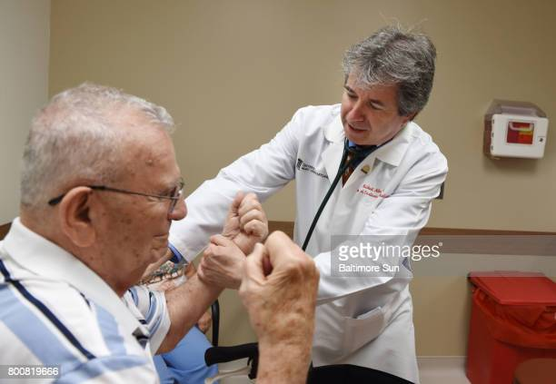 Dr Michael Miller right a professor of cardiovascular medicine checks the arm strength of Hank Butta during a consultation at his office at the...