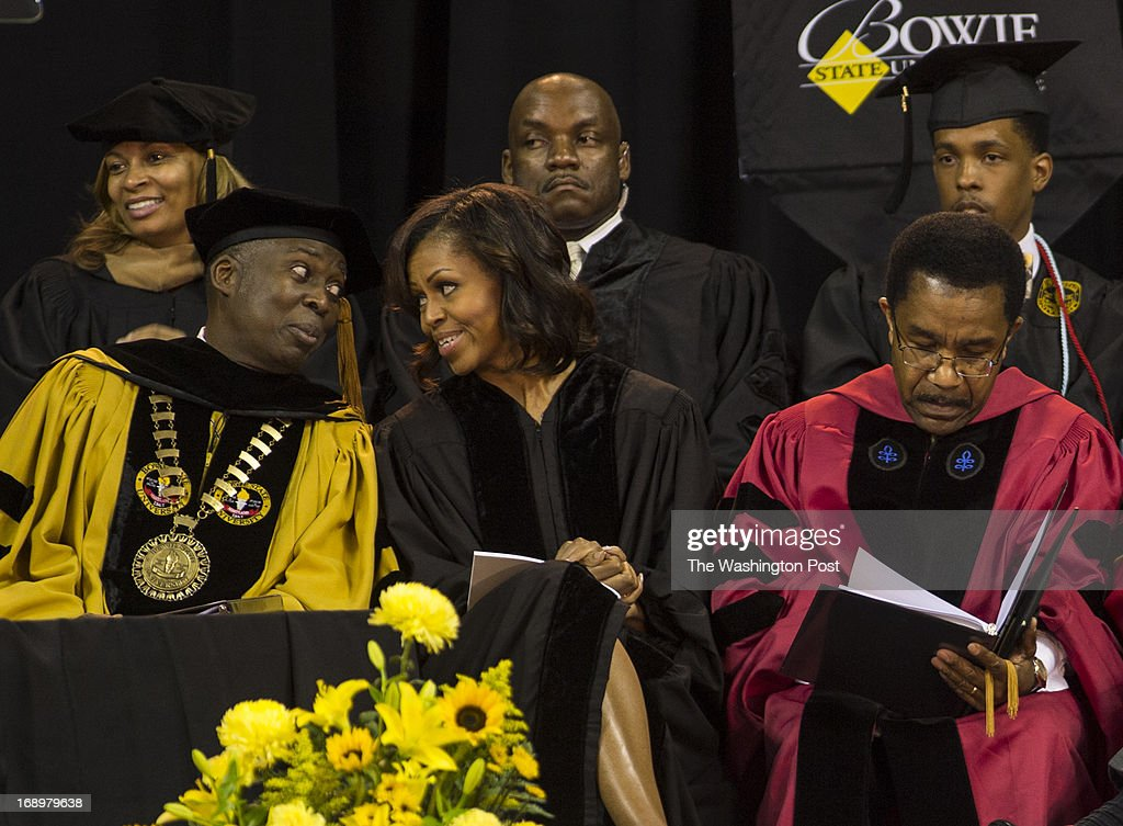 Dr. Mickey L. Burnim, President of Bowie State University, chats with First Lady Michelle Obama as Dr. Weldon Jackson, Provost and Vice President of Academic Affairs, consults the program during the 2013 graduation ceremony at Bowie State University held at the University of Maryland's Comcast Center in College Park, Maryland, on Friday, May 17, 2013. Mrs. Obama received an Honorary Doctorate of Laws.