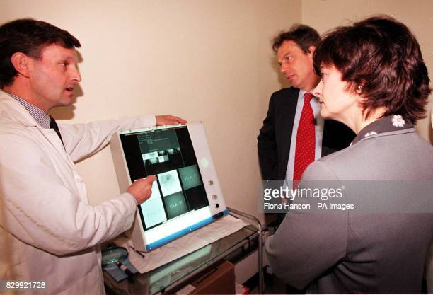 Dr Mike Michel explains xray examples to Prime Minister Tony Blair and his wife Cherie during a visit to the cancer unit at King's College Hospital...