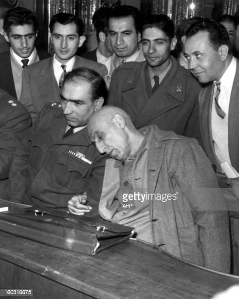 Dr Mohammad Mossadegh former Iran Prime Minister rests his head on his lawyer's shoulder during his trial in a military court 12 November 1953 He was...