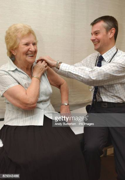 Dr Neil Horton giving Betty Hoskins from the 'So Graham Norton' show her flu jab during a photocall at a doctors surgery in Ladbroke Grove west...