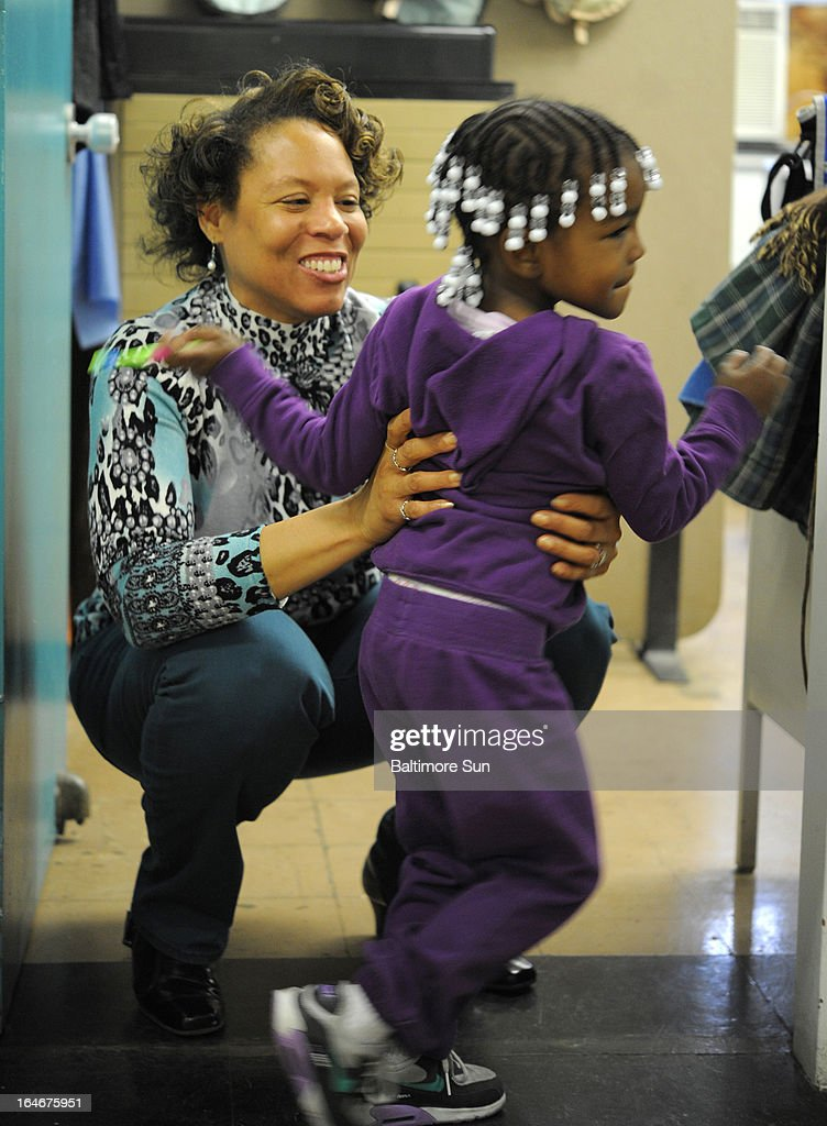 Dr. Patricia Bell-McDuffie, left, gets a hug from Mariah Venable, 3, after Venable was seen at the clinic, March 21, 2013, in Baltimore, Maryland. McDuffie oversees the cities dental clinic programs.