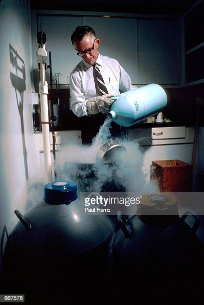 Dr Robert Graham founder of the Genius Sperm bank in San Diego Photographed filling liquid nitrogen into tanks that contain frozen sperm July 1982 Dr...