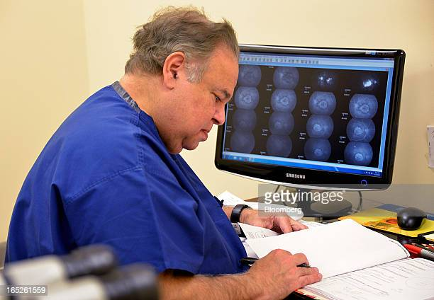 Dr Salomon Melgen makes notes in a patient's chart at his office in Port St Lucie Florida US on Thursday March 21 2013 Melgen spoke in his first...
