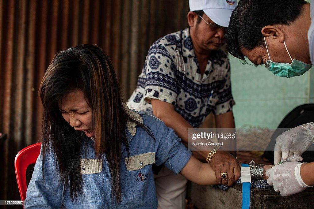Dr. Sari Mon from the Cambodian Ministry of Health takes a blood sample from a girl living near a poultry farm where the latest case of H5N1 had been detected August 26, 2013 in Krong Preak village, Kandal Province, Cambodia. Cambodia has seen the worst out break of Avian influenza H5N1 since the disease was first identified, so far this year 17 cases have been report, 10 of which have been fatal.