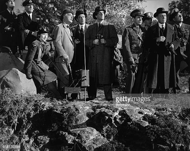 Dr Watson and Sherlock Holmes observe the tests of the new superbombsight which they have saved from the Nazis while members of the British cabinet...