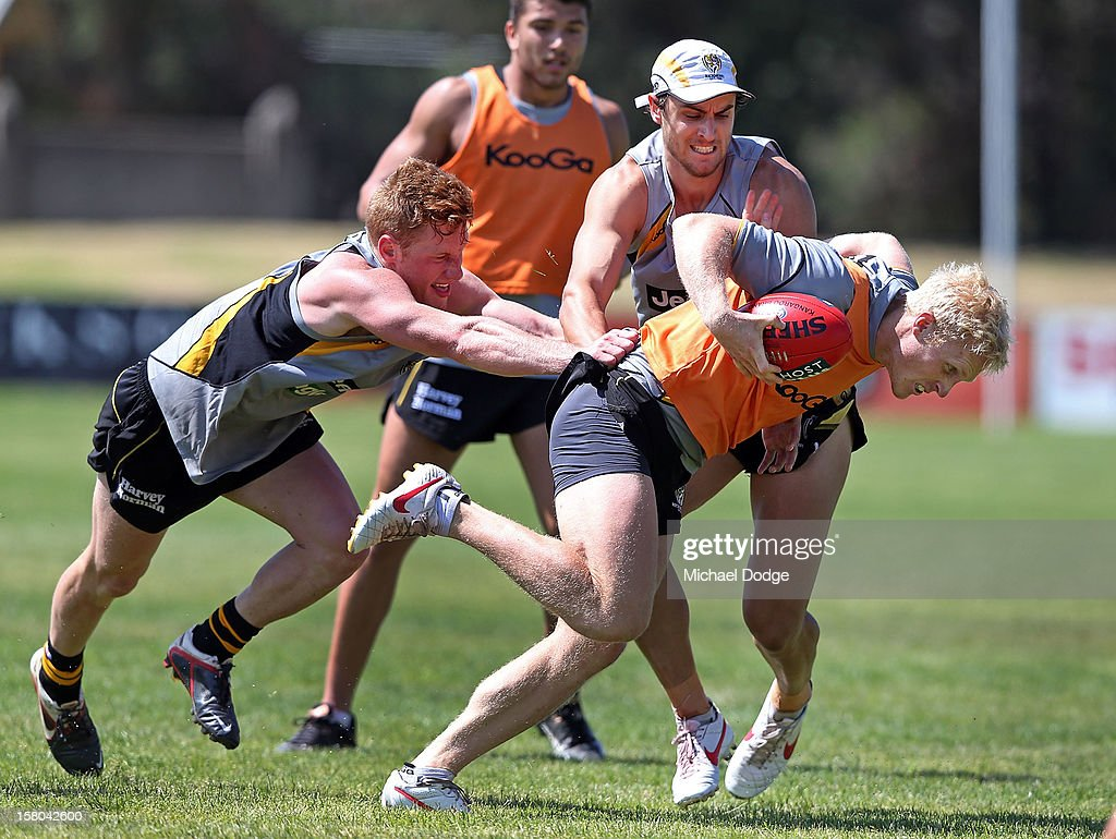 Draftee Nick Vlastuin (L) and Ben Griffiths tackle Steven Morris during a Richmond Tigers AFL training session at Trevor Barker Beach Oval on December 10, 2012 in Melbourne, Australia.