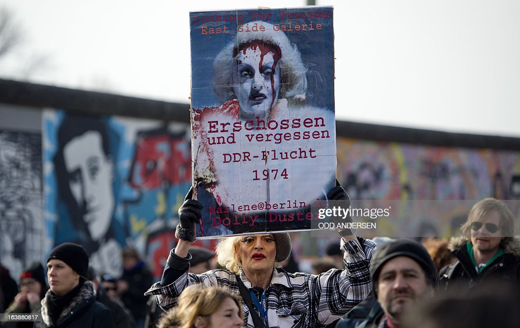 Drag artist Dolly Duster carries a banner that reads 'Shot and Forgotten, GDR escape 1974' within a crowd awaiting David Hasselhoff (not in pic) who tours the East Side Gallery on March 17, 2013 to protest the demolition of parts of the wall for a real estate project. The former Bay watch star was in the German capital to lend his support to the movement that wants to preserve the 1,3km long stretch of the cold war symbol and keep the land along river Spree as public land. AFP PHOTO / ODD ANDERSEN