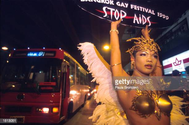 A drag queen holds up a sign that reads 'Stop AIDS' at the Bangkok Gay Festival and Parade December 1999 in Bangkok Thailand