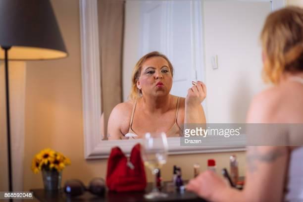 Drag queen mettre de maquillage sur devant le miroir