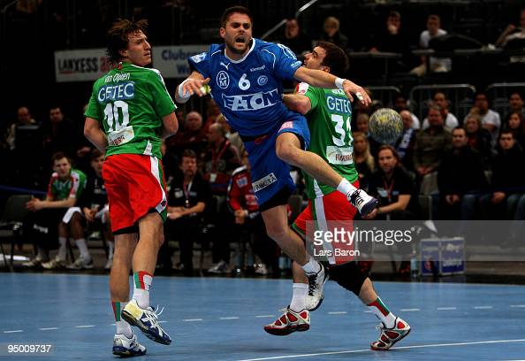 Drago Vukovic of Gummersbach is challenged by Fabian van Olphen and Bartosz Jurecki of Magdeburg during the Toyota Handball Bundesliga match between...