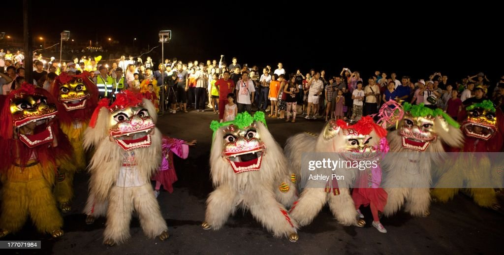 A Dragon and Lion dance is performed before a ceremony releasing water lanterns into the sea to celebrate the mid-summer Ghost Month Festival on August 20, 2013 in Keelung, Taiwan. Paper houses are burnt at sea to retrieve ghosts and lonely spirits of underworld through waterways leading back to the land as part of a Pudu (universal salvation) ritual. On the 14th day of the 7th lunar month, the gates of the underworld are opened for the spirits of the departed to come back to the land for a month long period of universal salvation in the land of the living.