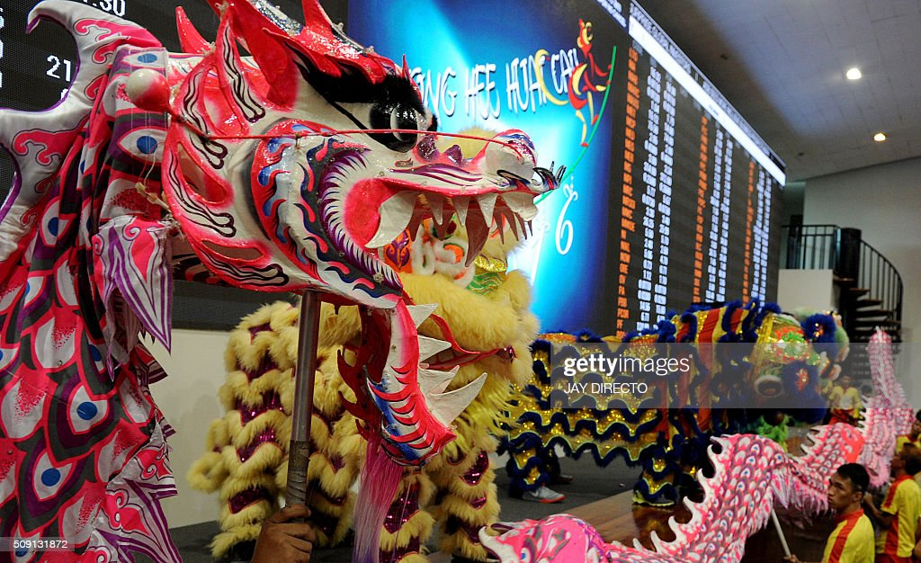 Dragon and lion dancers perform at the trading floor of the Philippine Stock Exchange to start the first day of trading for the Lunar New Year in Manila on February 9, 2016. AFP PHOTO / Jay DIRECTO / AFP / JAY DIRECTO