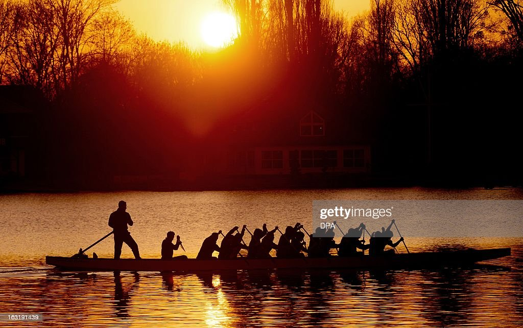 Dragon boat athletes silhouette against the sinking sun as they practice on Maschsee in Hanover, Germany, on March 5, 2013.
