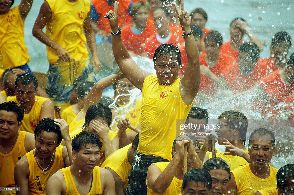 Dragon Boat competitors celebrate victory after competing in a race at Hong Kong's Aberdeen Harbour on June 4, 2003 in Hong Kong. Dragon boats compete against each other every June in remembrance of a famous Chinese poet and hero Qu Yuan, who drowned himself in the Mi Lo River as a protest against a corrupt government in the third century B.C. Legend says that in an attempt to rescue Qu Yuan, locals beat drums to scare fish away and threw dumplings into the sea to keep the fish from eating his body. (Photo by Christian Keenan/Getty Images