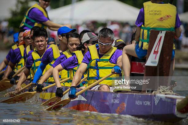 Dragon boat racers paddle their boats during Hong Kong Dragon Boat Festival on August 10 2014 in the Flushing Meadows neighborhood of the Queens...