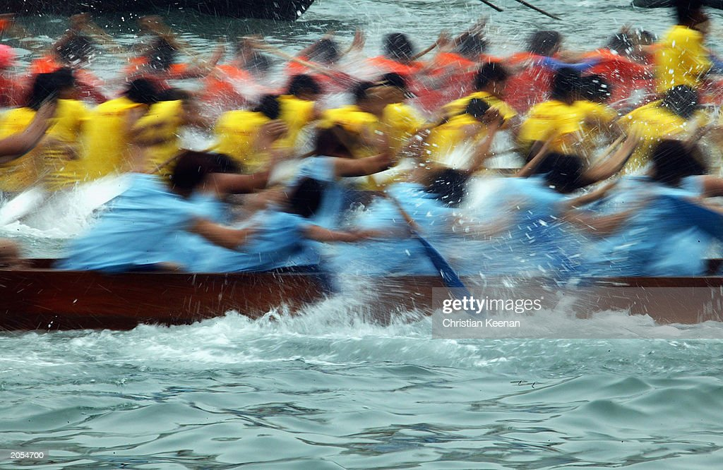 Dragon Boat teams participate in a race at Hong Kong's Aberdeen Harbour on June 4, 2003 in Hong Kong. Dragon boats compete against each other every June in remembrance of a famous Chinese poet and hero Qu Yuan, who drowned himself in the Mi Lo River as a protest against a corrupt government in the third century B.C. Legend says that in an attempt to rescue Qu Yuan, locals beat drums to scare fish away and threw dumplings into the sea to keep the fish from eating his body. (Photo by Christian Keenan/Getty Images