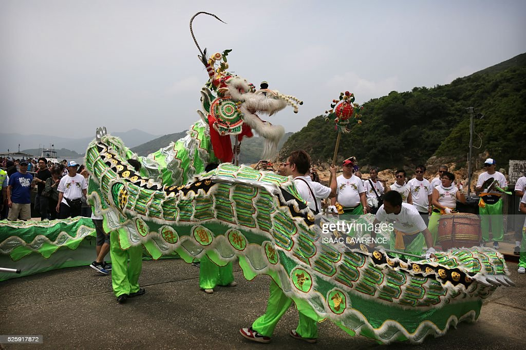 A dragon dance is performed outside the Joss House Bay Tin Hau temple during celebrations for the Tin Hau Festival in Hong Kong on April 29, 2016. Tin Hau is the Goddess of the Sea and patron saint of fishermen - On her birthday, locals flock to the more than 70 temples dedicated to her to pray for safety, security, fine weather and full fishing nets during the coming year. / AFP / ISAAC