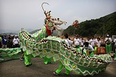 A dragon dance is performed outside the Joss House Bay Tin Hau temple during celebrations for the Tin Hau Festival in Hong Kong on April 29 2016 Tin...