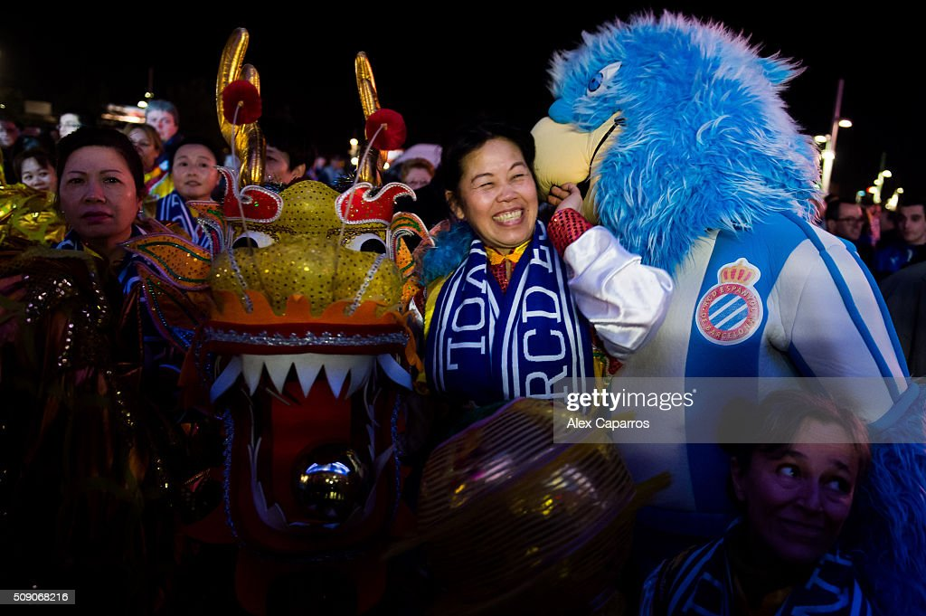 A dragon dance team member shares a joke with the mascot of RCD Espanyol during a Lunar New Year parade ahead of the La Liga match between RCD Espanyol and Real Sociedad de Futbol at Cornella-El Prat Stadium on February 8, 2016 in Barcelona, Spain.