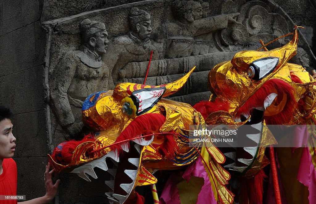 A dragon dancer waits to perform during a ceremony to mark the 224th anniversary of Vietnam's Dong Da victory over Chinese invading troops in the spring of 1789 at the site of the historical battlefield in Hanoi on February 14, 2013. AFP PHOTO/HOANG DINH Nam