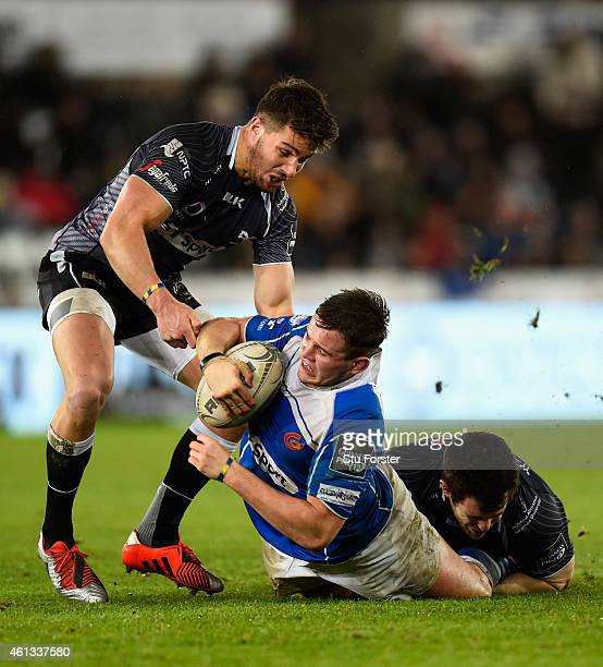 Dragons hooker Elliott Dee is tackled by Rhys Webb and Aaron Jarvis of the Ospreys during the Guinness Pro 12 match between Ospreys and Newport Gwent...