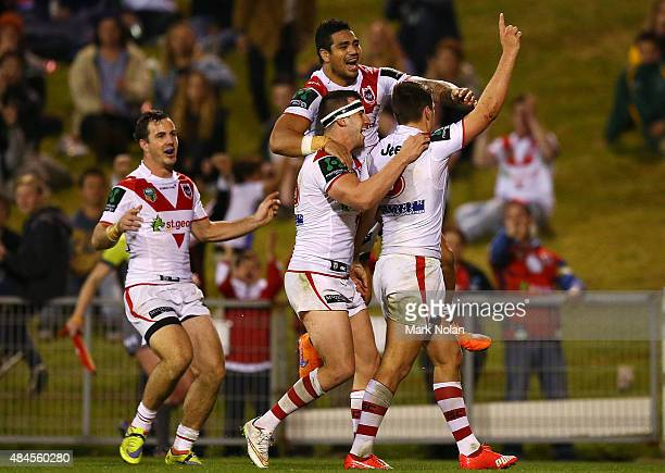 Dragons players celebrate a try by Gareth Widdop during the round 24 NRL match between the St George Illawarra Dragons and the Penrith Panthers at...