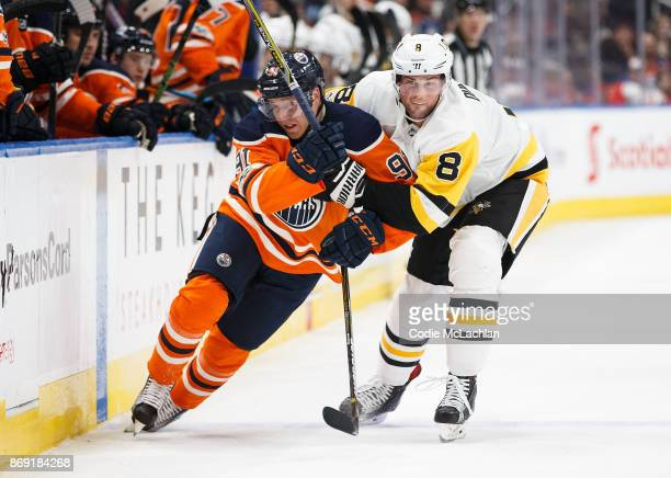 Drake Caggiula of the Edmonton Oilers battles with Brian Dumoulin of the Pittsburgh Penguins at Rogers Place on November 1 2017 in Edmonton Canada