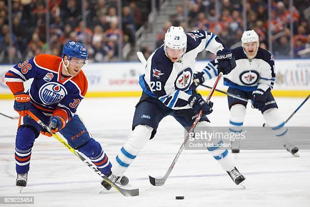 Drake Caggiula of the Edmonton Oilers harasses Patrik Laine of the Winnipeg Jets on December 11 2016 at Rogers Place in Edmonton Alberta Canada