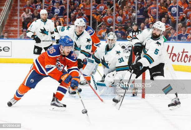Drake Caggiula of the Edmonton Oilers is defended by David Schlemko of the San Jose Sharks in Game Five of the Western Conference First Round during...