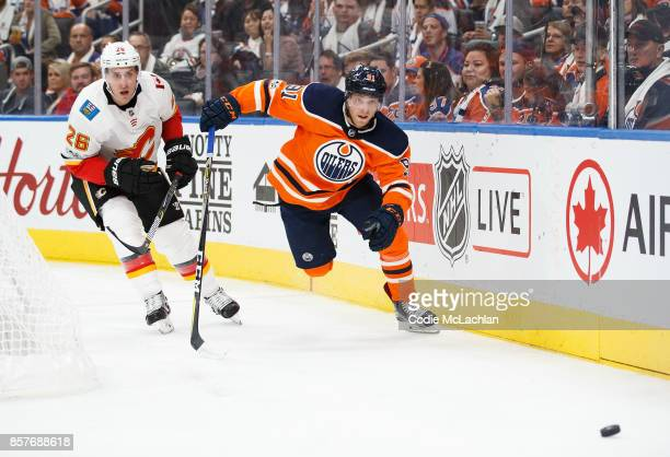 Drake Caggiula of the Edmonton Oilers is pursued by Michael Stone of the Calgary Flames at Rogers Place on October 4 2017 in Edmonton Canada