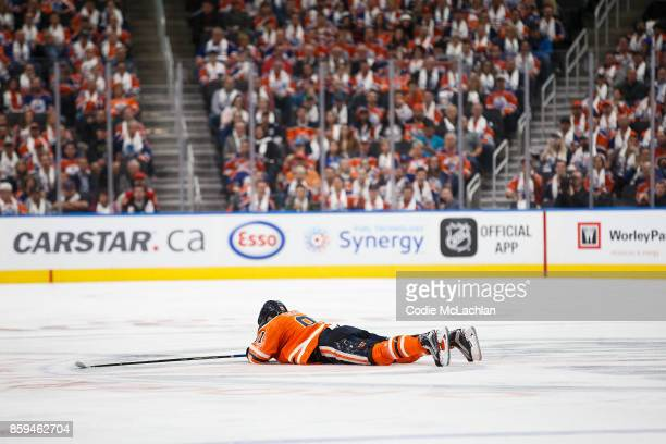 Drake Caggiula of the Edmonton Oilers lies on the ice after taking a hit while skating against the Calgary Flames at Rogers Place on October 4 2017...