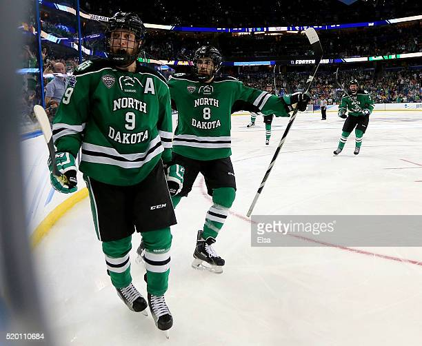 Drake Caggiula of the North Dakota Fighting Hawks celebrates his goal during the third period against the Quinnipiac Bobcats as teammate Nick...