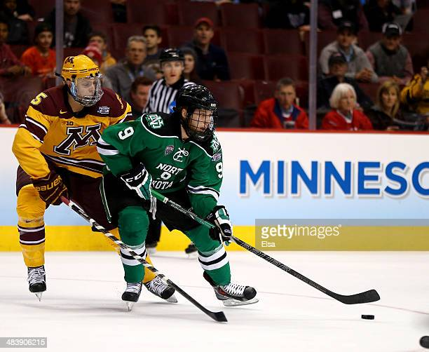 Drake Caggiula of the North Dakota Fighting Sioux takes the puck as Mike Reilly of the Minnesota Gophers defends in the first period during the 2014...