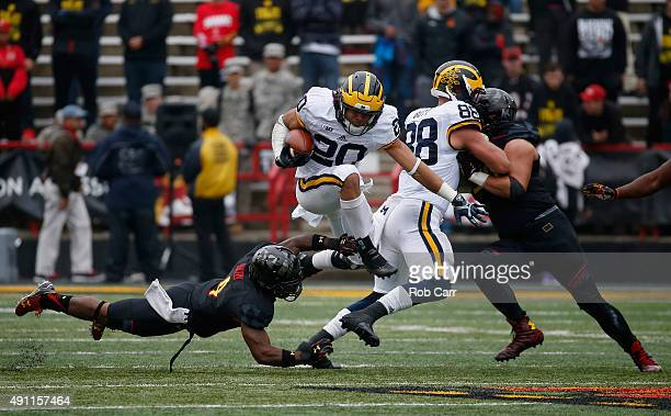 Drake Johnson of the Michigan Wolverines jumps over William Likely of the Maryland Terrapins while carrying the ball in the second half of the...